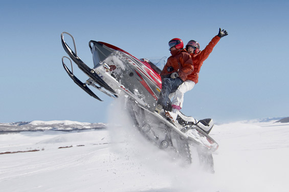two people in winter attire on a jet ski in the snow
